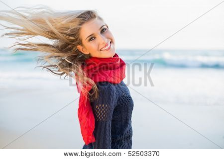 Cheerful sexy blonde tossing her hair on a beautiful wild beach
