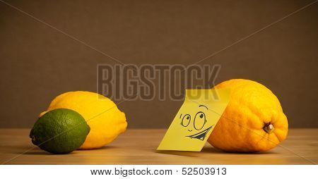 Lemon with sticky post-it note reacting at citrus fruits