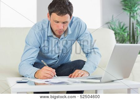 Serious casual man writing on sheets paying bills in bright living room