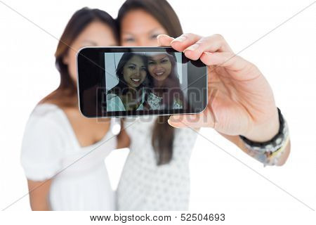 Two smiling asian sisters taking a self portrait using a smartphone