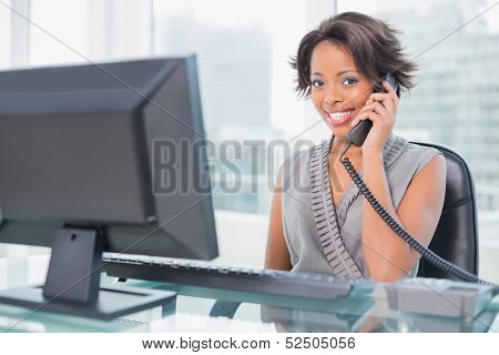 Smiling businesswoman talking on phone while looking at camera in her office