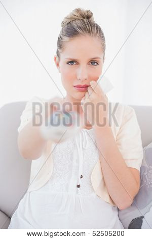 Anxious fresh model changing tv channel sitting on sofa in bright living room