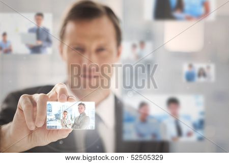 Pleased businessman picking a business team picture among blurred others