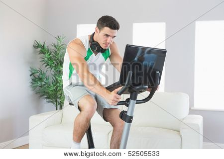 Stern handsome man training on exercise bike using laptop in bright living room