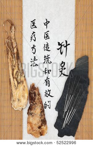 Acupuncture needles with angelica herb root and mandarin script on rice paper. Dang gui pian. Translation describes acupuncture chinese medicine as a traditional and effective medical solution.