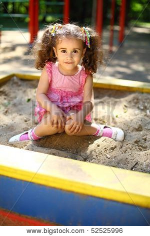 Little girl with tails sitting in the sandbox