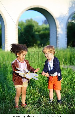 The boy shows a wind spinner to the girl