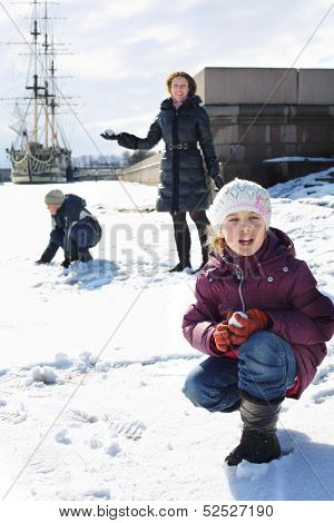 Mother with two children playing a snowball fight next to a sailboat