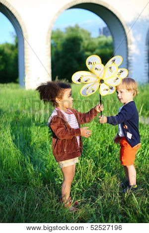 The boy passes wind spinner to the girl