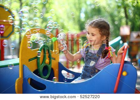 Little girl with pigtails blowing soap bubbles with a pistol on the playground