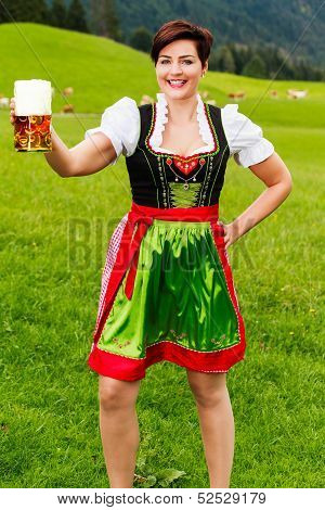Happy young woman in a dirndl with a beer