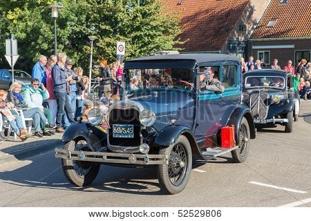 Oldtimer cars in a countryside parade during a Dutch agricultural festival