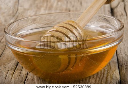 Honey And Dripper In A Small Glass Bowl