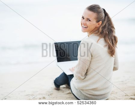 Smiling Young Woman In Sweater Sitting On Lonely Beach And Using Laptop