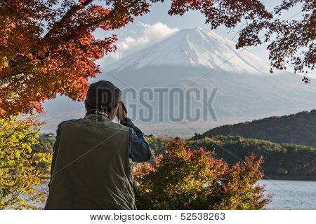 MOUNT FUJI - NOVEMBER 7: A man photographs Mount Fuji through fall foliage November 7, 2012 in Mount Fuji, JP. Viewing of seasonal foliage has been a popular past time in Japan for centuries.