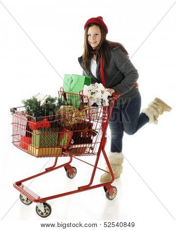 An attractive preteen in outdoor clothes rushing with a red shopping basket full of Christmas goodies.  On a white background.