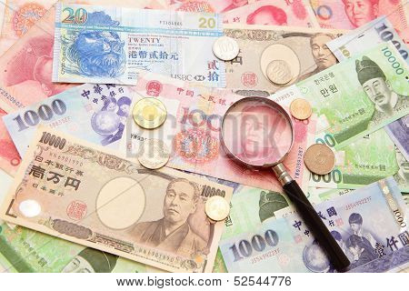 Asian Currency, Magnifying Glass And Background Of Asian Currency