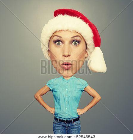 surprised bighead girl in santa hat over grey background