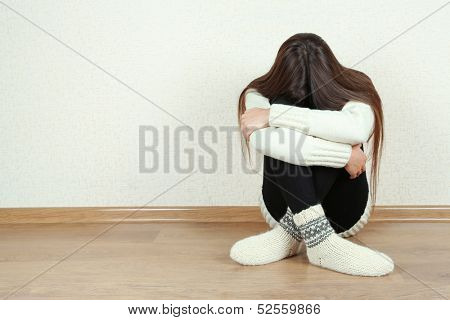 Sad woman sitting on floor near wall