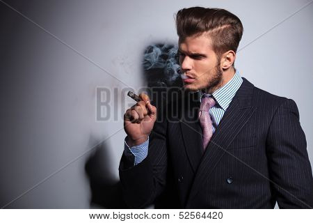side view of a fashion model in suit and tie enjoying his cigar on gray background