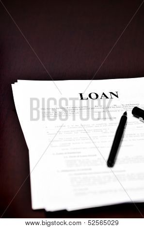 Loan Document on desk with black pen waiting to be signed