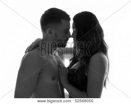 Sexy and romantic couple wearing lingerie embracing each other and about to kiss in a black and white photo