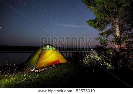 Illuminated tent in a forest and night sky with stars