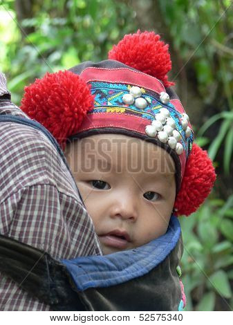 Yao hilltribe baby in traditional headdress, Northern Laos