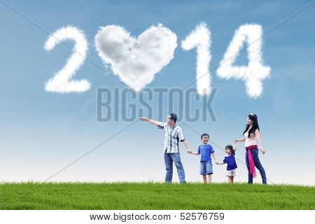 Family Having Fun Under Cloud Of New Year 2014