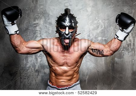Young man in boxing gloves and gladiator helmet posing