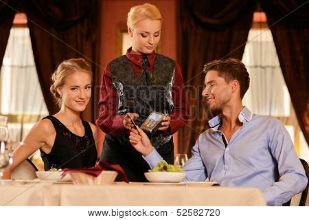 Beautiful young couple paying with card in a restaurant
