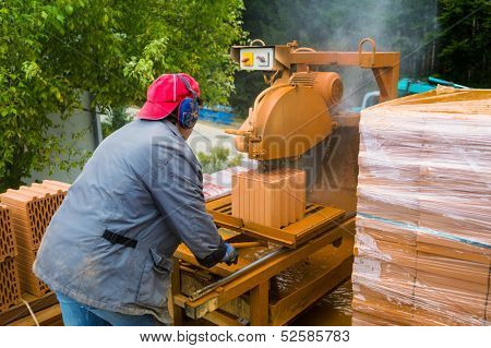 construction worker cuts bricks for the construction of a detached house in massive construction