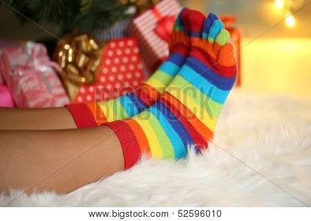 Legs in socks near Christmas tree on carped