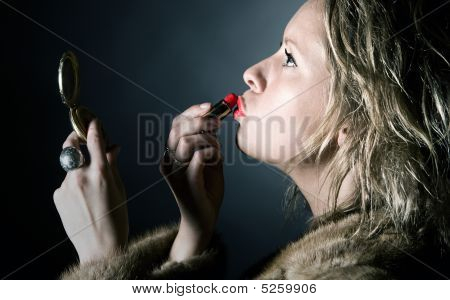 Shot Of A Vintage Styled Female Applying Her Red Lipstick