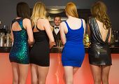 Attractive friends ordering drinks from barkeeper at nightclub poster