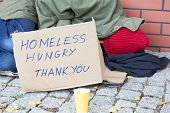 stock photo of begging  - Homeless hungry poor man sleeping on a street - JPG
