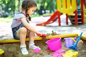 Little girl with pigtails sitting in the sandbox and playing with molds