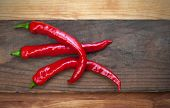 image of jimmy  - Three red peppers on rustic old board background - JPG