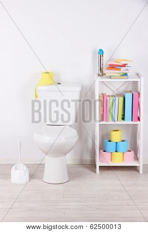 White toilet bowl and stand with books, on color wall background