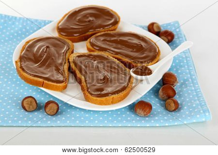 Bread with sweet chocolate hazelnut spread on plate isolated on white