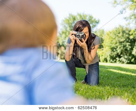 Happy young woman photographing baby son through camera in park