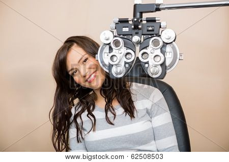 Portrait of happy young woman sitting behind phoropter during eye exam