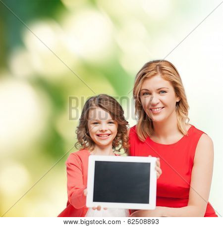 family, child and technology concept - smiling mother and daughter with tablet pc computers blank black screen