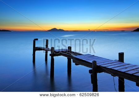 Wooden bridge with seascape during sunet