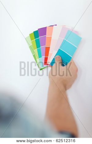 repair, building, technology and home concept - close up of male with color pallets choosing color