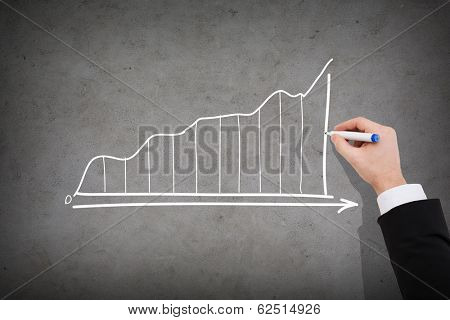 business and economics concept - close up of businessman drawing growing graph on concrete wall