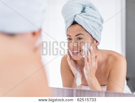 middle aged woman cleaning her sking over the sink