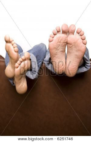 Man And Woman's Feet Over Back Of Couch
