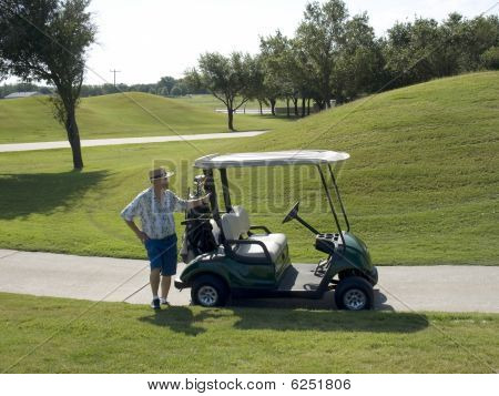 Senior Standing By The Golf Cart