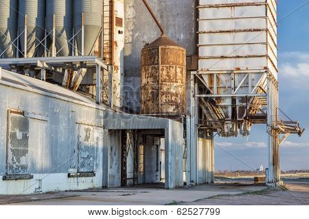 old grain elevator with pipes, ducts, ladders and chutes, a distant rural landscape of northern Colorado